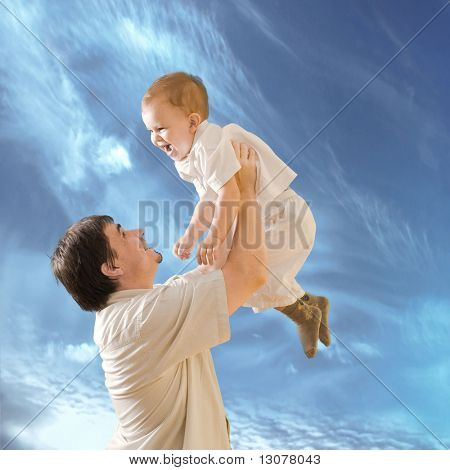 Father is lifting 2 years old baby boy.