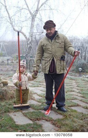 Grandpa and grandson spend time together outdoor in the garden on a cold winter day.