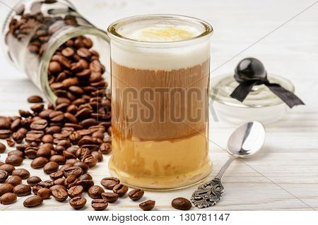 Coffee latte macchiato and coffee beans on white wooden background.