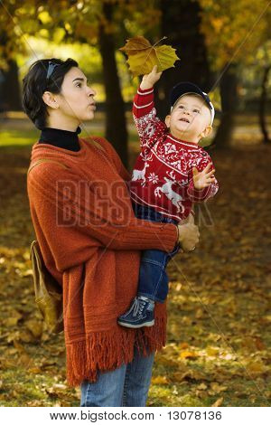 Baby and mother are playing together with fallen leaves.