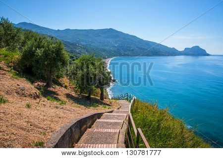 A stone staircase descending to the coast