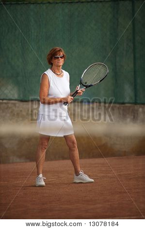 Active senior woman in her 60s plays tennis.