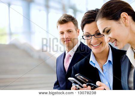 Jóvenes empresarias compartir información en los teléfonos móviles. Enfoque selectivo se coloca sobre la mujer en el medio