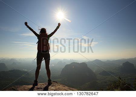 cheering woman open arms on sunrise mountain peak
