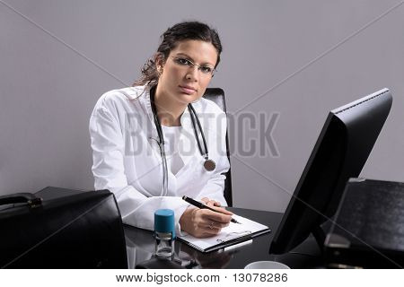 Young female doctor works on her desk.