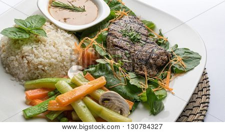 Thick cut beef filet steak served with rice vegetables mushroom and gravy sauce on white porcelain dish
