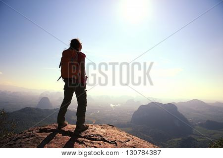 successful woman hiker at sunrise mountain peak