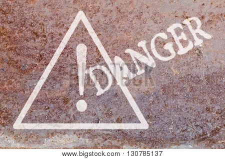 on the old rusty sheet painted white triangle with an exclamation mark and the words Danger