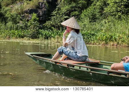 A female tourist riding on boat whilst the trip to Tam Coc caves in Hoa Lu capital located in Ninh Binh, Vietam. On the background limestone karst mountains are seen covered by lush greeneries.
