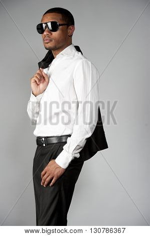 An attractive African American male carrying a custom suit over his shoulder with sunglasses posing in a studio setting on a gray background.