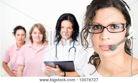 Young female cinic receptionist wearing glasses and headset, medical team in background. Isolated on white.