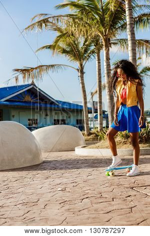 Beautiful Teenage Black Girl In Blue Skirt Stand With Her Penny Longboard.
