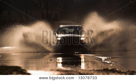 Car is driving through a water-course by high speed.