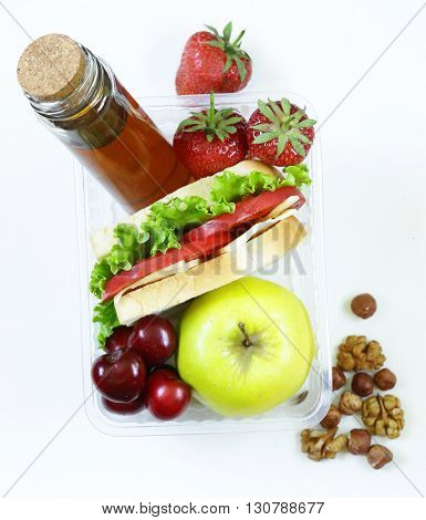 Healthy school lunch box with apple, nuts, berries and sandwich