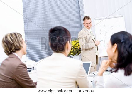 Three businesswoman sitting at desk, making notes. Businessman explaining on whiteboard. Selective focus placed on the trainer in background.