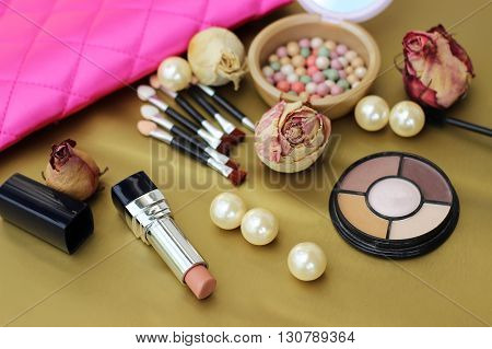 Cosmetics set for makeup and decorations on the gold background