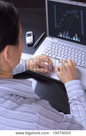 Young businesswomen works on a laptop computer and reads financial analysis.