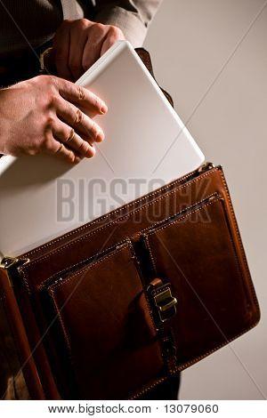 Homem de negócios abrir pasta de couro marrom elegante para tirar o computador portátil.