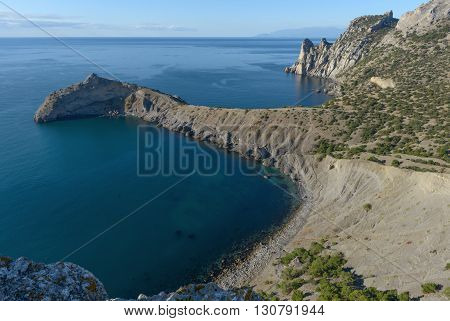 High angle scenic view of ''Sinyaya'' (Blue) or Pirate Cave towards Kapchik Cape Light Blue or King or Delimanskaya Cave and Chicken-Kaya Cape is from western side of Koba-Kaya Mountain near New World (Novyi Svet) town Crimea Russia.