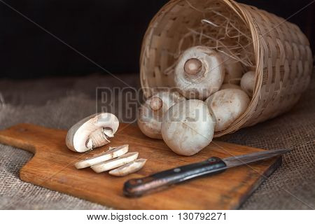 White mushrooms closeup sliced lying on a cutting wooden board with a knife. Wicker basket full of champignon
