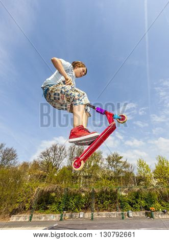 Boy Is Jumping With A Scooter Over A Spine In The Skate Park