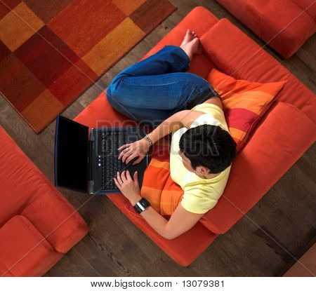 Young woman is sitting and resting on the sofa and using a laptop computer. Maybe she is surfing the net, chatting or studying for the next university exam.