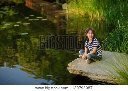 On the shore of the pond is sitting cross-legged boy. He smiles. The picturesque pond surrounded by green bulrush