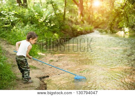 little boy fishing in river in forest river