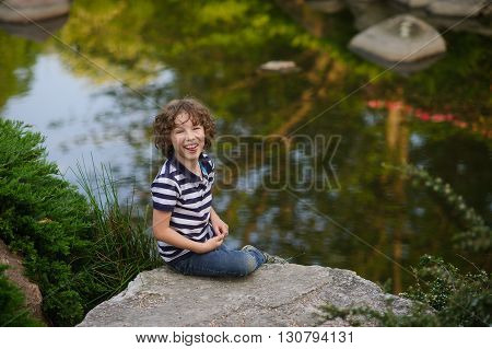 8-9 years boy sitting on a big stone near the pond. The child laughs. He stuck out his tongue