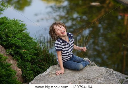 Blonde boy 8-9 years old sitting on a large rock in a pond. He laughs merrily. Behind the boy's beautiful pond
