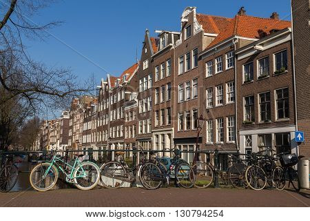 AMSTERDAM NETHERLANDS - 17TH FEBRUARY 2016: Buildings and bikes in the Centrum district of Amsterdam during the day.