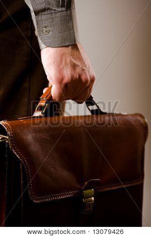 Homem negócios, segurando a pasta de couro marrom elegante.