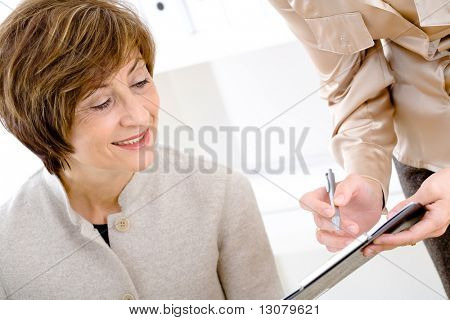 Happy senior businesswoman reviewing documents at office, smiling.