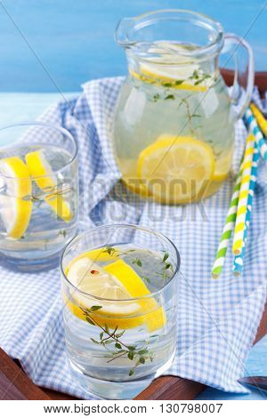 Cool beverage with lemon and thyme in a tray on blue wooden background