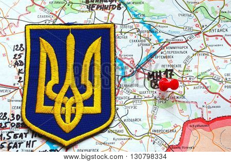Illustrative editorial.Chevron of Ukrainian Army. Eastern Ukraine map with site of MH-17 flight crash as background. At April 25,2016 in Kiev, Ukraine