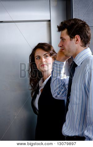 Businessman and businesswoman walking on office corridor and calling on mobile phone.