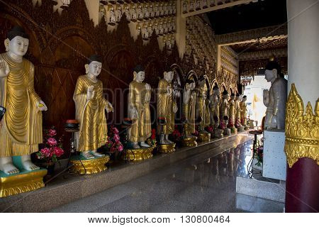 Gold draped Statues of Buddhas line a hallway in the kek Lok Si Temple complex