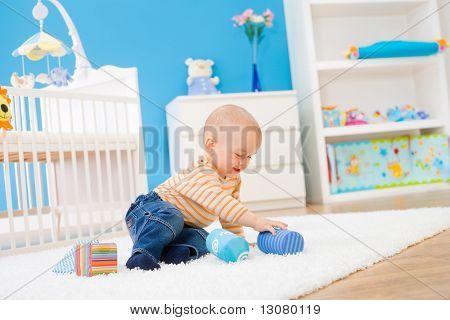 Happy baby boy (1 año de edad) sentado en el piso en el cuarto de los niños y jugando con bloques de juguete. Ar de juguetes