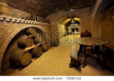 A table and wine barrels stacked in the old cellar of the winery.