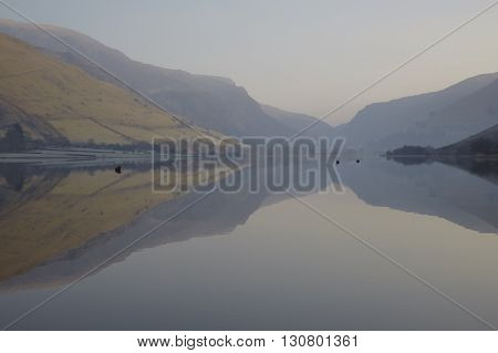 Mountains reflecting in the still water of Tal-y-Llyn lake in Snowdonia North Wales on a calm summer morning.