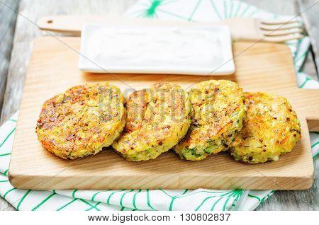 Quinoa Zucchini feta dill fritters on a white wooden background.