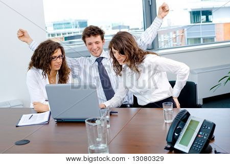 Happy successful business people sitting on meeting at office, working on laptop computer, smiling.