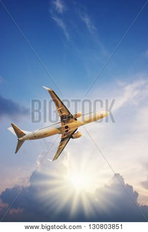 Airplane with sun ray on blurred sky sunset in twilight
