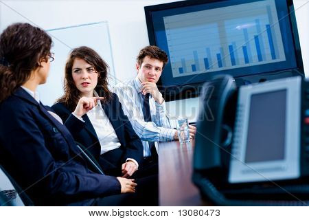 Young serious businesspeople talking in meeting room at office, phone and plasma TV.