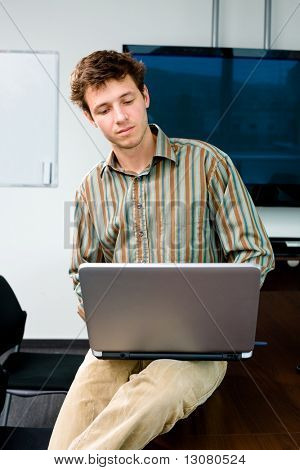 Young office worker sitting on meeting table at office and working on laptop computer.