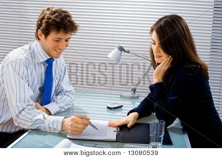 Businessman and businesswoman working together in team at office, smiling.