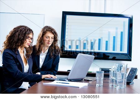 Young businesswomen sitting by meeting table at office in front of a huge blank plasma TV screen and using laptop and phone.