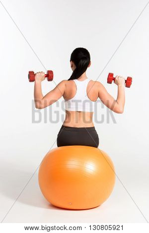 Young beautiful sportswoman doing fitness exercise with dumbbells on pilates ball, at studio shot. Health, beauty and fitness concept.