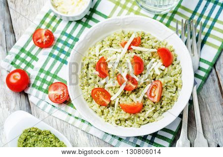 Pesto rice with tomatoes and cheese on white wood background.