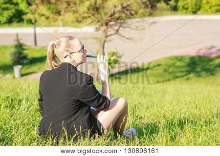 young beautiful woman sitting on the grass and writing in a notebook